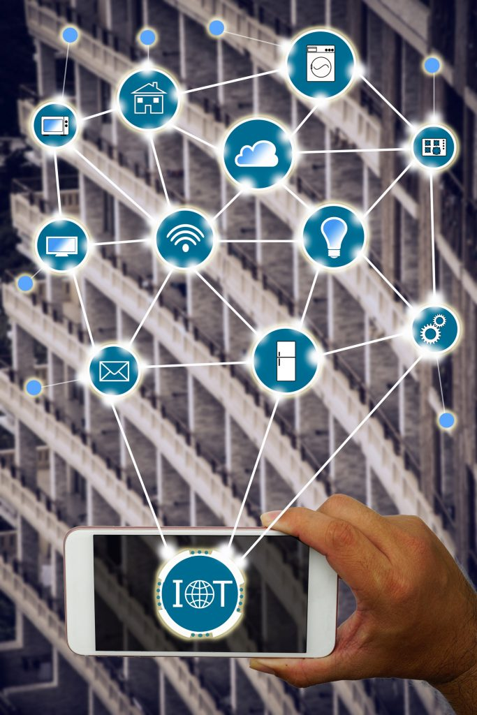 Internet of things (IOT) concept : Hand holding smartphone controlling various household equipment with building background. Smart home concept, Smart Building Concept.